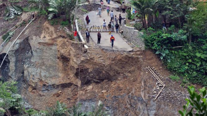 Sejumlah warga menyaksikan jalan raya yang ambles di lokasi bencana longsor di Desa Clapar, Madukara, Banjarnegara, Jateng, Rabu (30/3/2016).