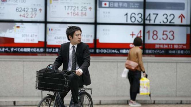 Pengendara sepeda di depan papan Bursa Saham Tokyo.