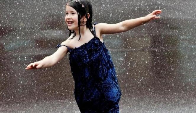 Anak bermain air hujan.