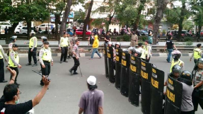 Ilustrasi polisi hadang massa yang ingin bentrok.