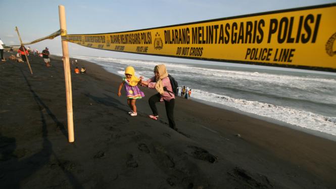 Sejumlah wisatawan berjalan di belakang garis polisi yang dipasang di bibir Pantai Trisik, Kabupaten Kulon Progo, Yogyakarta, Minggu (10/7/2016).