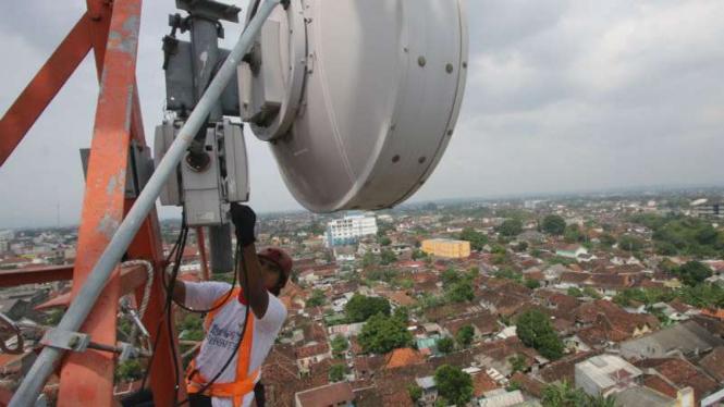 Petugas memperbaiki base transceiver station (BTS).