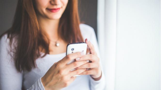 Ilustrasi wanita bermain handphone.