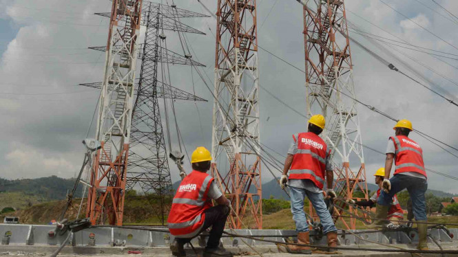 Pekerja memasang kawat baja sebelum pengujian tower transmisi listrik milik PLN. Foto ilustrasi