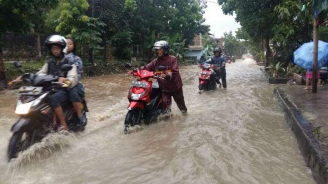 Sejumlah pengendara sepeda motor mendorong kendaraannya yang mogok akibat banjir di jalur alternatif Gedebage Kota, Bandung, Jawa Barat,  pada Jumat, 28 Oktober 2016.