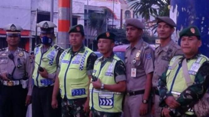 Anggota Polresta Depok dibantu TNI dan Sat Pol PP melakukan pengamanan Lomba Lari 10 K di jl. Margonda Raya Depok.