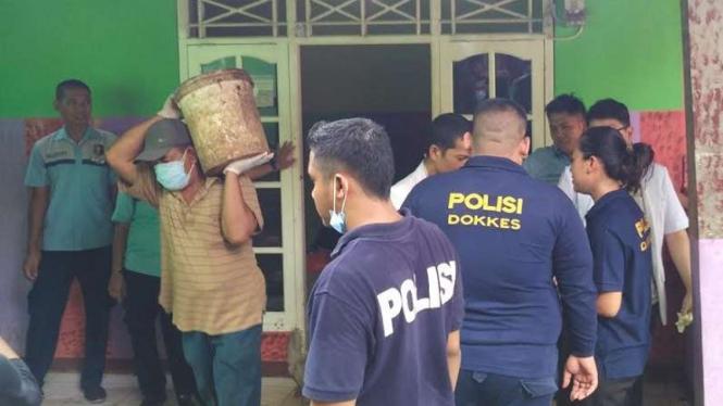 Petugas kepolisian gali lantai tempat Sopyan dikubur dan disemen.