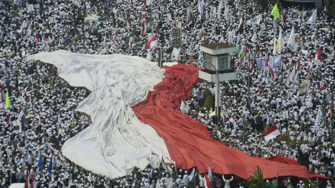 Umat Muslim kibarkan bendera Merah Putih saat aksi unjuk rasa.