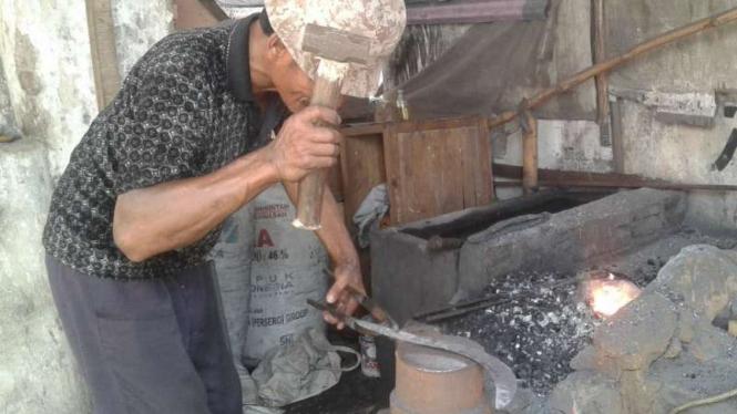 Mulyadi, pande besi di Kota Malang, tengah membuat clurit.