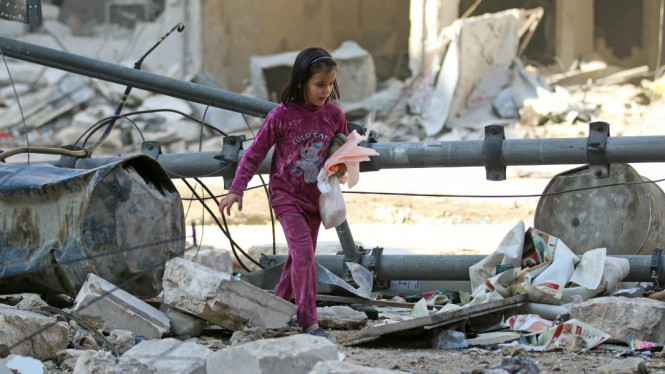 Seorang bocah berjalan di antara bangunan yang runtuh akibat serangan udara di Aleppo Suriah 17 November 2016. Menurut PBB, Aleppo telah menjadi kuburan massal.