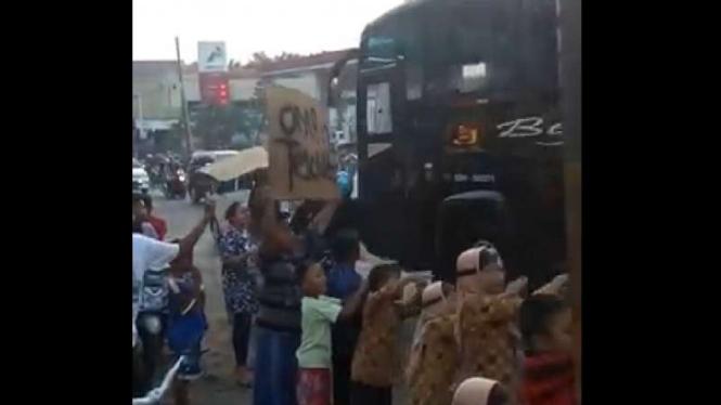 Aksi anak-anak meminta bus melintas membunyikan klakson telolet.
