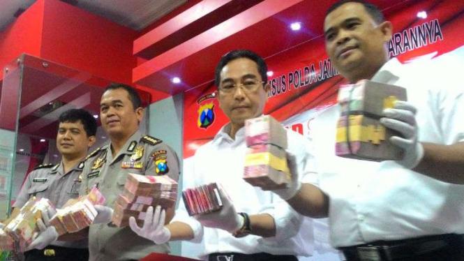 Polisi membeberkan uang hasil sitaan pungli dana desa di Kecamatan Kedungdung, Kabupaten Sampang, Madura, di Markas Polda Jatim, Surabaya, pada Rabu, 7 Desember 2016.