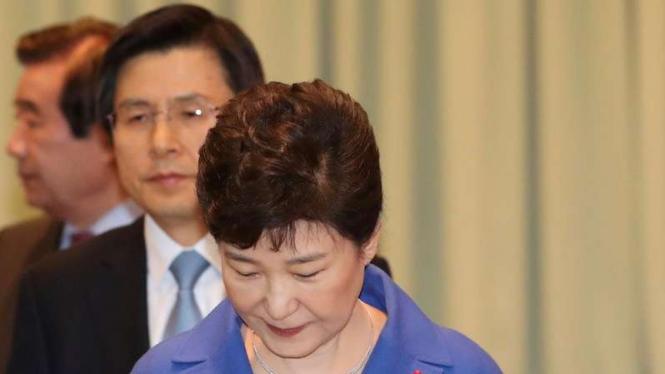 Presiden Korea Selatan, Park Geun-hye, (depan) dipecat dan posisinya diganti sementara oleh Perdana Menteri Hwang Kyo-ahn (belakang tengah).
