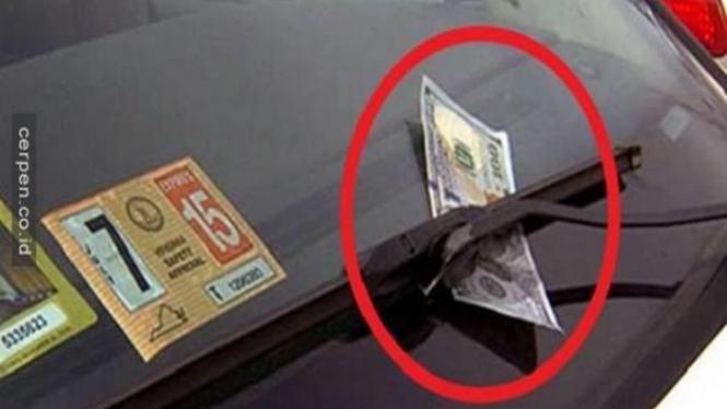 Uang diselipkan di wiper mobil.