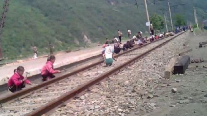 Anak-anak di Korea Utara bekerja memperbaiki rel kereta api.