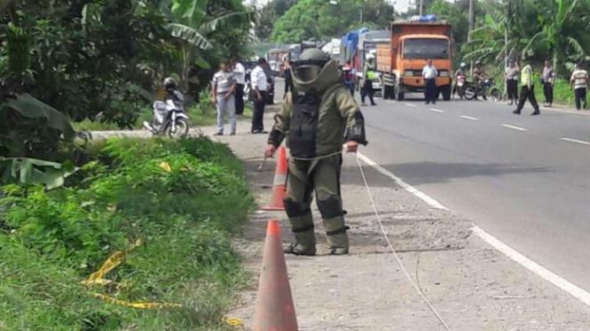 Petugas penjinak bahan peledak Polda Jawa Timur memeriksa sebuah benda yang awalnya dicurigai bom di Jalan Raya By Pass Mojokerto-Surabaya pada Kamis, 22 Desember 2016.