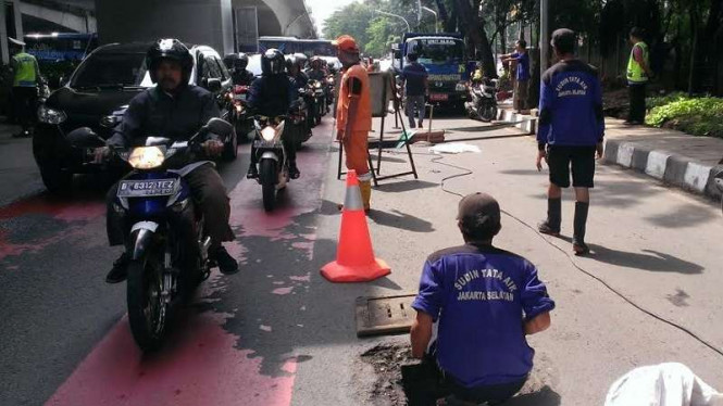 Pasukan oranye dan biru membersihkan gorong-gorong di kawasan Kuningan, Jakarta.