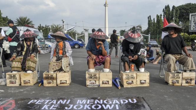 Para petani Kendeng saat beraksi memasung kaki dengan adonan semen di dekat Istana Negara sebagai bentuk protes mereka atas pendirian pabrik semen di Rembang, Jawa Tengah.