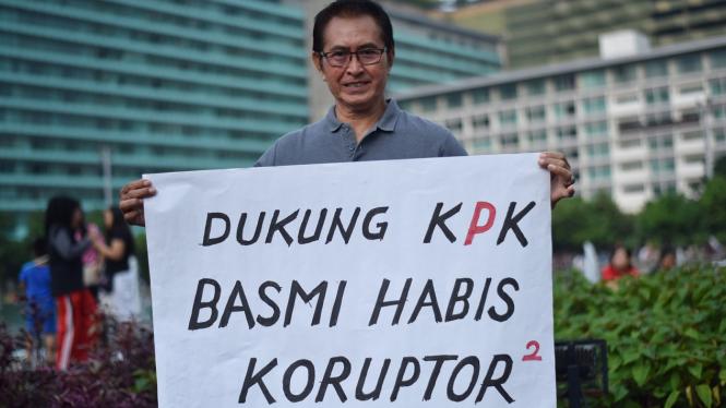 Aktor senior Pong Harjatmo melakukan aksi dengan membawa poster ketika pelaksanaan Hari Bebas Kendaraan Bermotor di Kawasan Bundaran HI Jakarta.