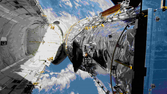 Teleskop Hubble ditangguhkan di atas pesawat ulang alik Discovery