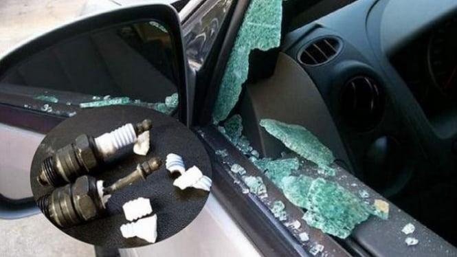 Serpihan busi pecahkan kaca mobil.