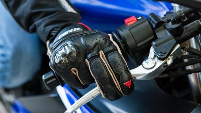 Ilustrasi menarik tuas rem motor dengan dua jari.