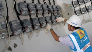 Petugas PLN memeriksa meteran listrik.