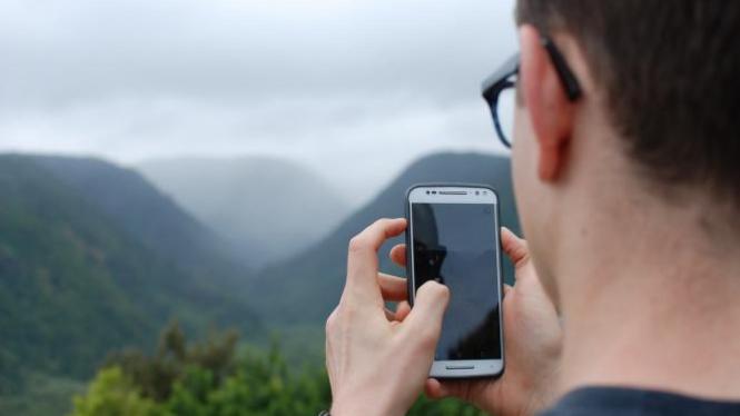Ilustrasi cek sinyal ponsel di daerah terpencil.