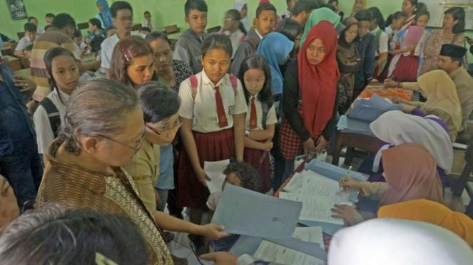 Calon siswa beserta wali murid antre pendaftaran penerimaan peserta didik baru (PPDB) SMP melalui sistem zonasi di SMPN 2 Tulungagung, Tulungagung, Jawa Timur, Senin (12/6/2017).