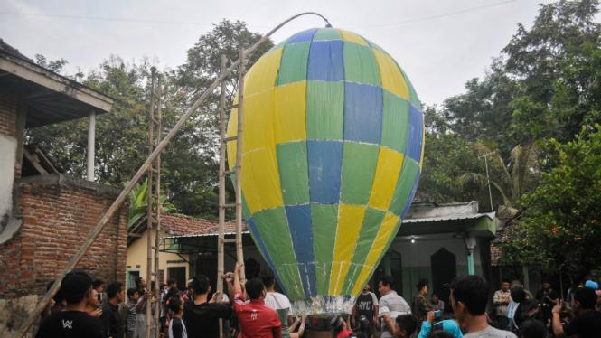 Warga menerbangkan balon udara di Desa Bandung, Kecamatan Diwek, Kabupaten Jombang, Jawa Timur, Minggu (2/7). Tradisi menerbangkan balon udara raksasa bersamaan di tiap musholah ini untuk merayakan Lebaran Ketupat atau biasa disebut Kupatan.