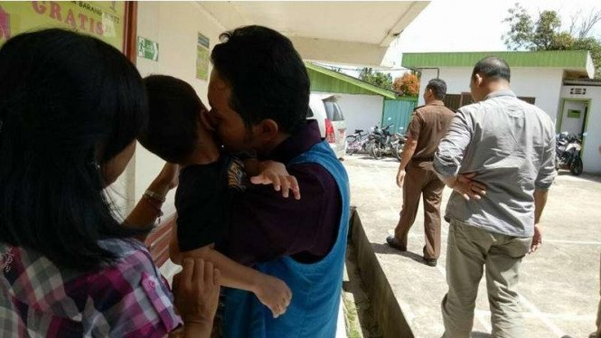 Fidelis Arie Sudewarto mencium anak bungsunya di PN Sanggau Kalimantan Barat. Pria ini divonis 8 bulan penjara karena menanam ganja untuk obat istrinya.