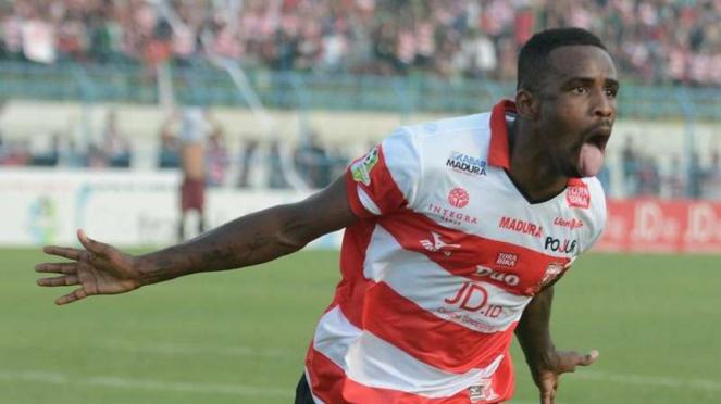 Pemain Madura United, Greg Nwokolo, melakukan selebrasi gol.