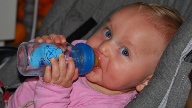 Ilustrasi bayi minum dari botol susu.