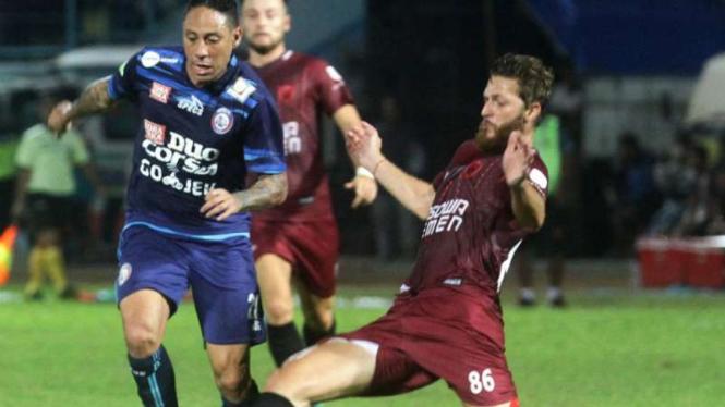 Pesepak bola Arema FC Juan Pablo Pino (kiri) saat berhadapan dengan PSM Makassar