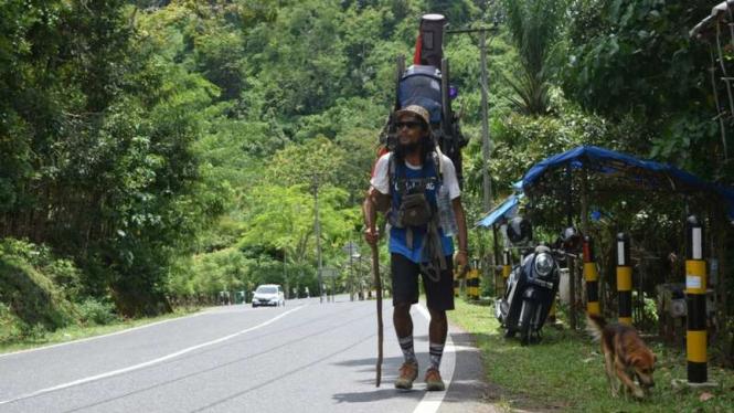 Safir dan anjingnya Batu, berjalan kaki di ruas jalan Gunung Parau Aceh Besar, Kamis (31/8/2017). Sebelas bulan sudah Safir berjalan kaki menyusur Pulau Sumatera.