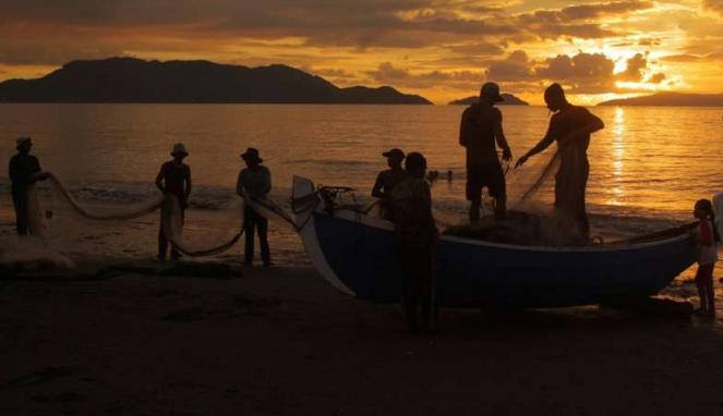 Nelayan menarik jala di sore hari di Pantai Gampong Jawa, Banda Aceh