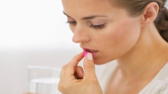 Ilustrasi wanita minum obat.