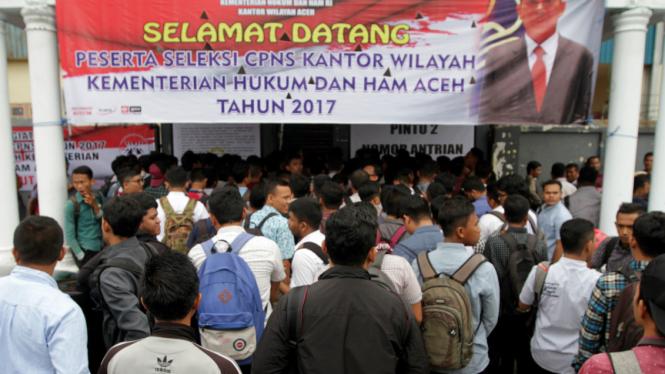 Peserta ujian Calon Pegawai Negeri Sipil (CPNS) Kementerian Hukum dan HAM wilayah Aceh antre seleksi pengukuran tinggi badan di Banda Aceh, Aceh, Senin (11/9).