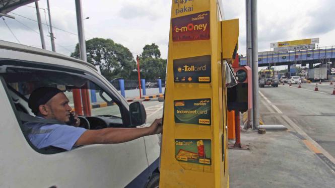 Seorang pengemudi mobil pengguna jalan tol bertransaksi menggunakan kartu elektronik non tunai ketika akan keluar dari tol Belmera Amplas Medan, Sumatera Utara