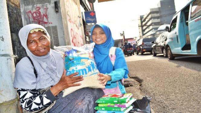 Ibu penjual tisu menerima bantuan sembako.