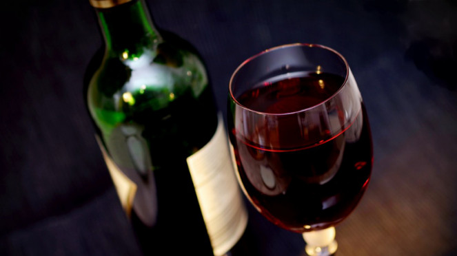 Segelas arak anggur merah atau red wine.