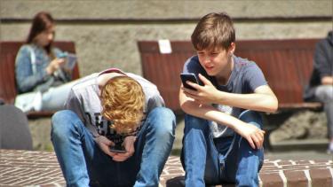 Ilustrasi anak main gadget atau smartphone.
