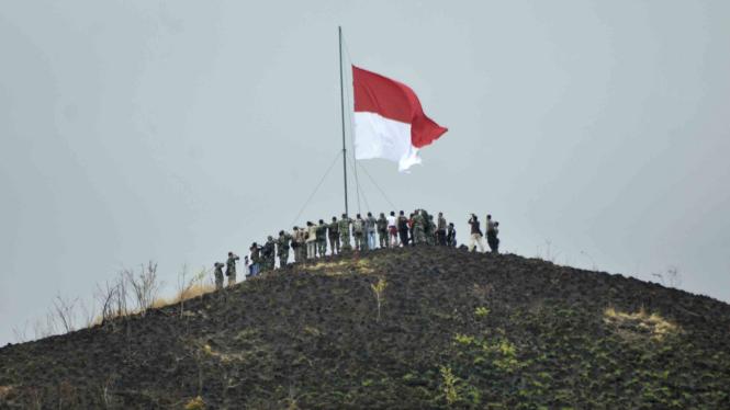 Warga yang tergabung dalam Persatuan Gabungan Lintas Masyarakat (Panglima) bersama TNI dan Polri menggelar upacara pengibaran bendera Merah Putih di Bukit Piramida, Desa Lampanah Leungah, Seulimum, Kabupaten Aceh Besar.