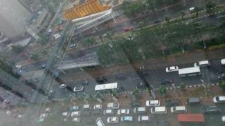 Lalu lintas di Jalan Jenderal Sudirman arah Semanggi padat, cuaca hujan.