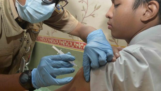Seorang siswa SMA Negeri 33 mendapatkan imunisasi serentak atau Outbreak Response Immunization (ORI) Difteri, di Cengkareng, Jakarta.