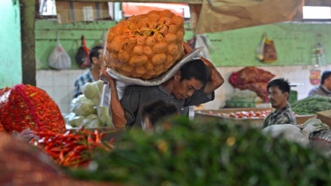 Pedagang mengangkut bahan pangan di pasar. (Foto ilustrasi)