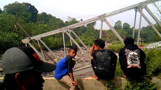 Warga menonton jembatan yang ambruk.