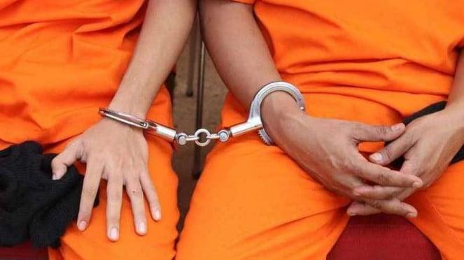 Ilustrasi tersangka pelaku kejahatan diborgol oleh polisi.