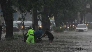 Ilustrasi polisi bantu warga saat banjir.