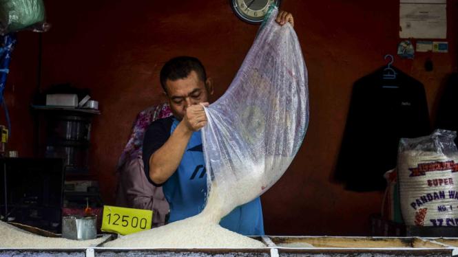 Pekerja mengisi wadah beras di Pasar Kosambi, Bandung. (ilustrasi sembako kena PPN)